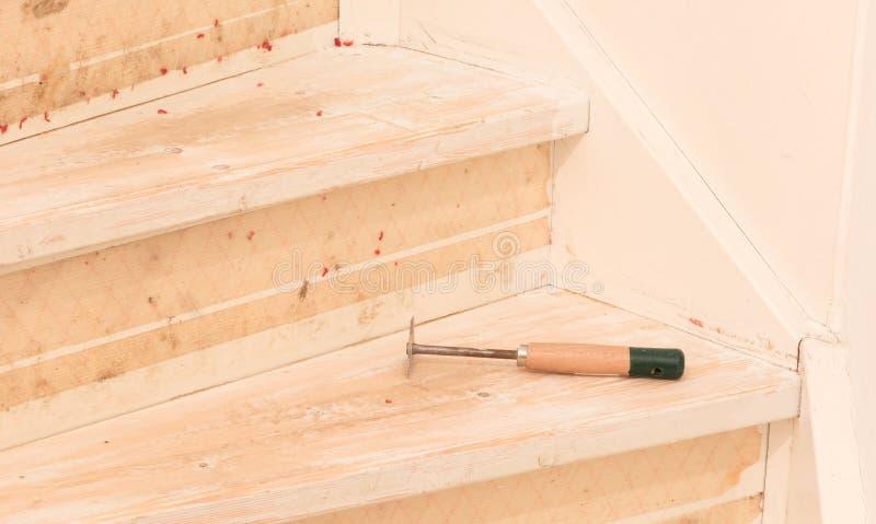 Eliminación de la alfombra, del pegamento y de la pintura de las escaleras de un vintage fotos de archivo