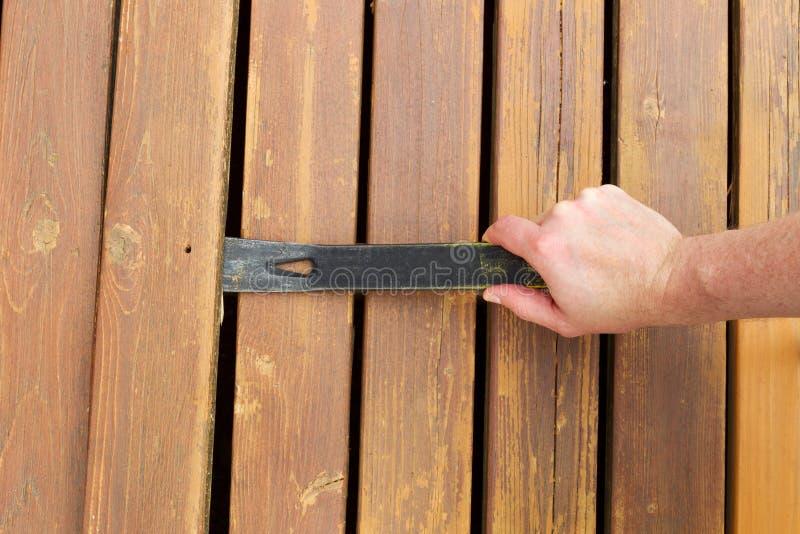 Eliminación de los viejos tableros de madera con la barra de palanca fotos de archivo