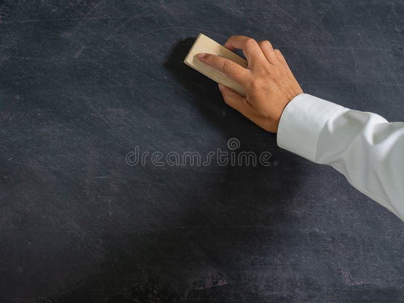 Eliminador da escova da terra arrendada da mão e quadro-negro, educação do conceito e fotografia de stock royalty free