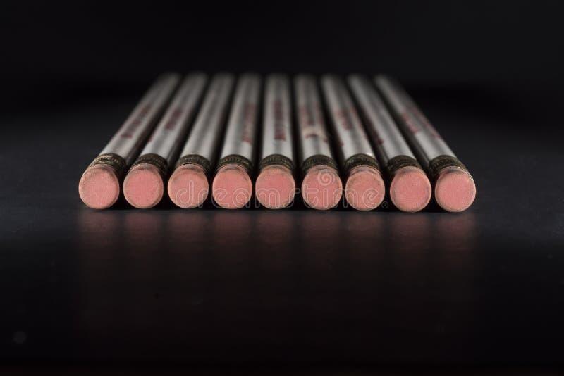 Eliminadores de lápis na superfície preta fotografia de stock