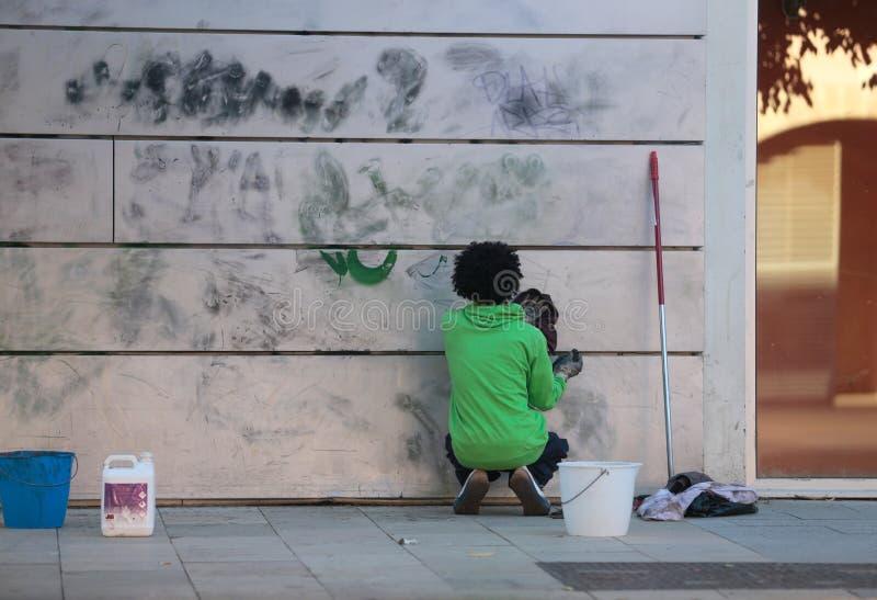 Eliminazione delle pitture dei graffiti fotografia stock