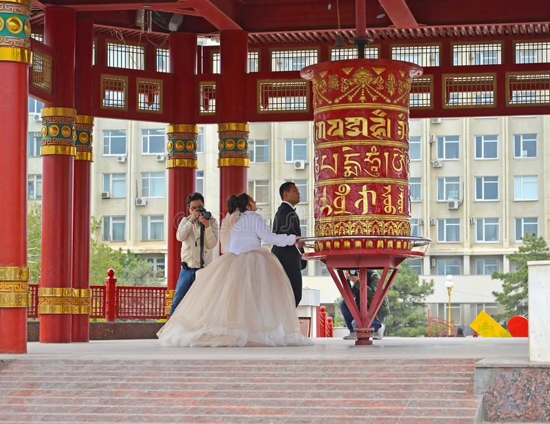 ELISTA, RUSSIA. The groom and the bride spin a prayer wheel with a mantra of Ohms of Manya Padme Hum. Pagoda of Seven Days royalty free stock photo