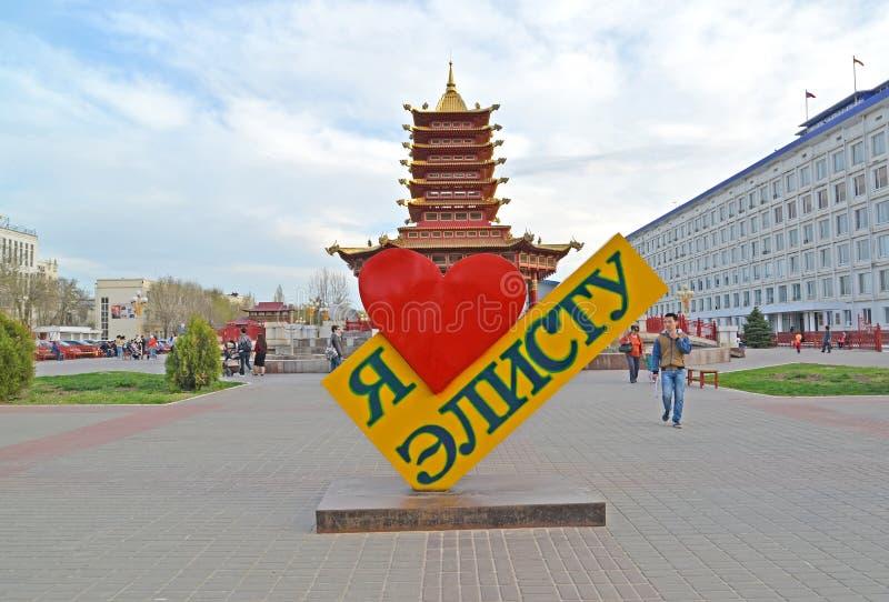 ELISTA, RUSSLAND Ein Stele ` I Liebe Elista-` vor dem hintergrund einer Pagode von sieben Tagen Lenin-Quadrat stockfotografie