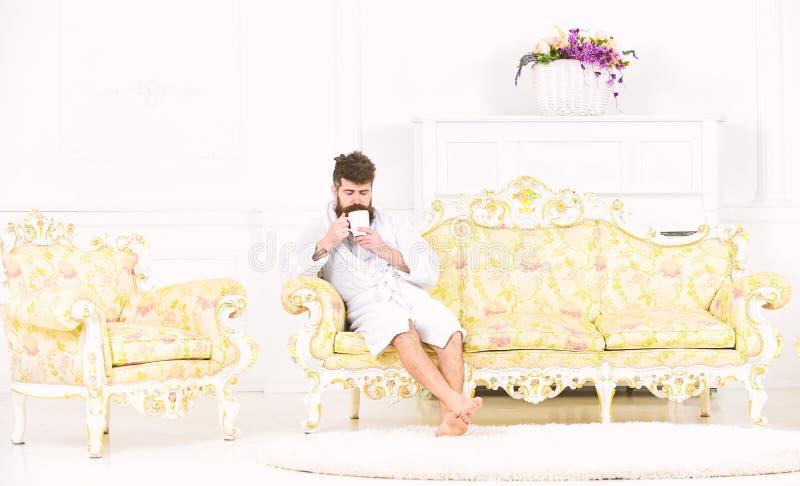 Elita czasu wolnego pojęcie Mężczyzna z brodą i wąsy cieszy się ranek podczas gdy siedzący na luksusowej kanapie Mężczyzna na śpi obrazy royalty free