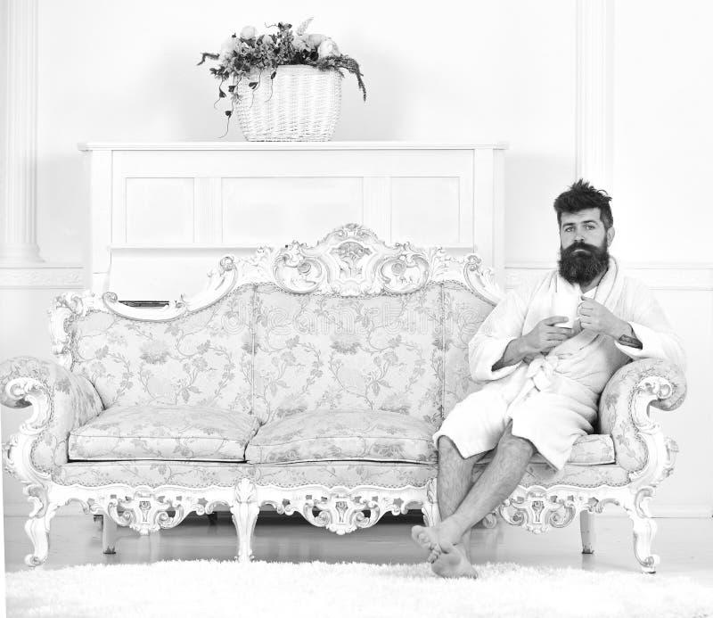 Elita czasu wolnego pojęcie Mężczyzna na śpiącej twarzy w bathrobe, napój kawa w luksusowym hotelu w ranku, biały tło człowieku obrazy stock