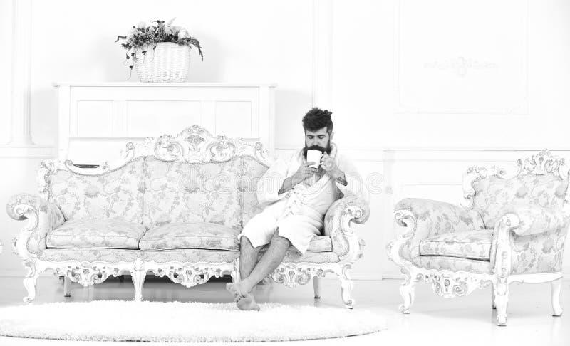 Elita czasu wolnego pojęcie Mężczyzna z brodą i wąsy cieszy się ranek podczas gdy siedzący na luksusowej kanapie Mężczyzna na śpi fotografia stock