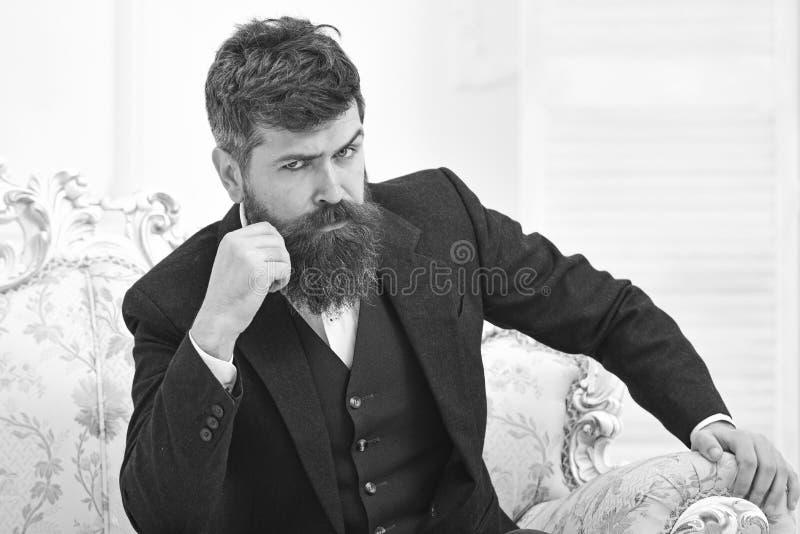Elita stylu życia pojęcie Mężczyzna jest ubranym klasycznego kostium z brodą i wąsy, siedzimy na staromodnym karle lub kanapie ma obraz royalty free