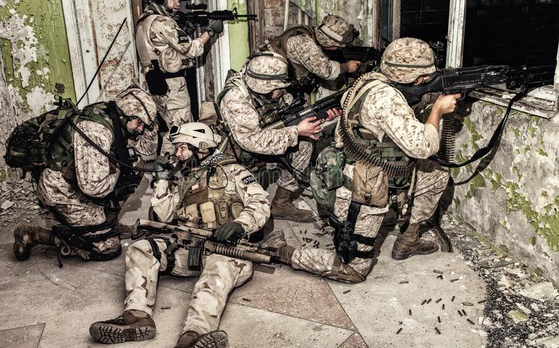Elite assault squad keeping defense in city fight. Special operations forces soldiers team, commando assault squad keeping defense under fire in abandoned royalty free stock photo