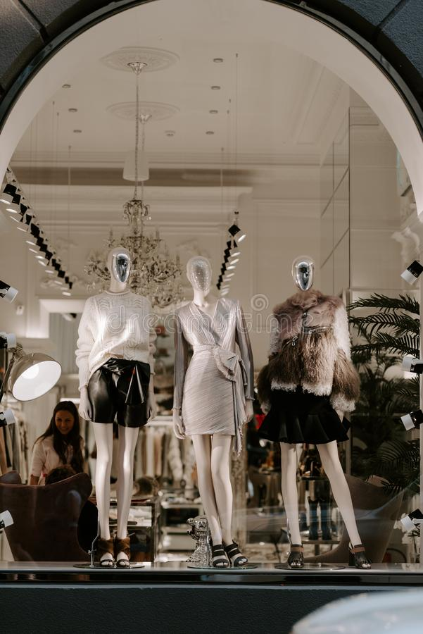 Elite boutique display window with mannequins in fashionable dresses. Fashion fall winter Trend. Fashionable clothes in boutique. royalty free stock photography