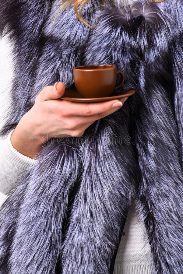 Elite coffee concept. Female hand fur coat hold brown cup or mug. Drink coffee little ceramic cup close up. Enjoy royalty free stock images
