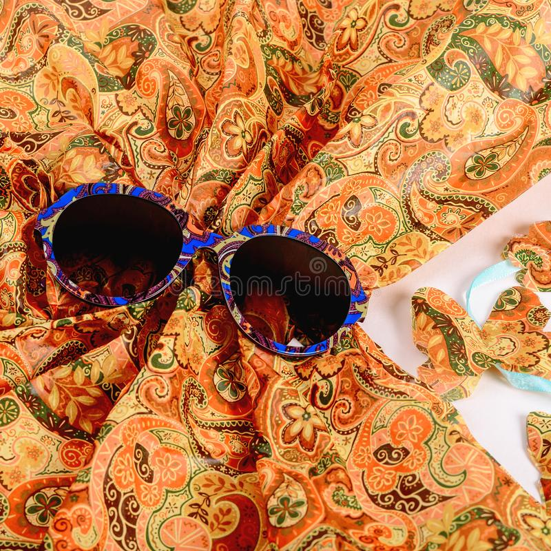 Elite Sunglasses in a modern fashionable frame on the background of the scarf royalty free stock photo