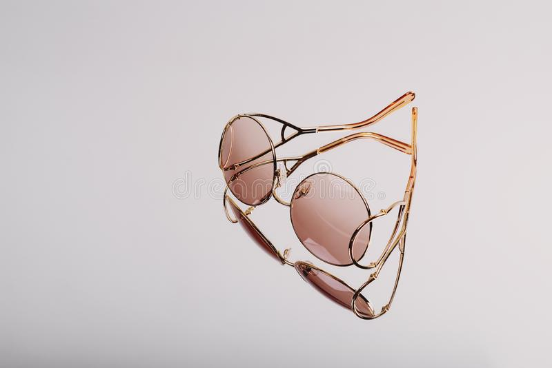 Elite Sunglasses in a modern fashionable golden metal frame on a silver background stock photo