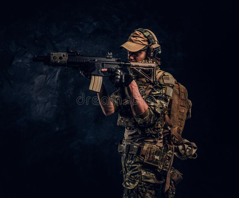 The elite unit, special forces soldier in camouflage uniform holding an assault rifle with a laser sight and aims at the stock photo