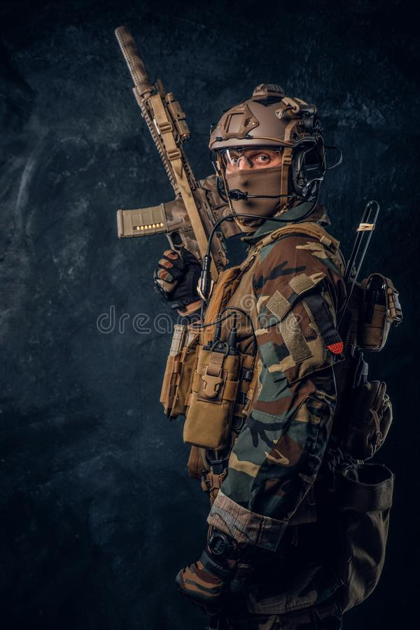 Elite unit, special forces soldier in camouflage uniform posing with assault rifle. stock photography