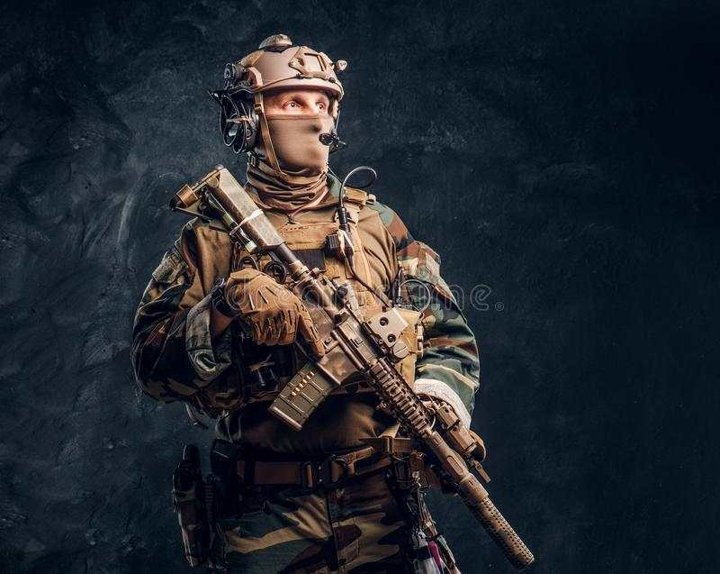 Elite unit, special forces soldier in camouflage uniform posing with assault rifle. stock images