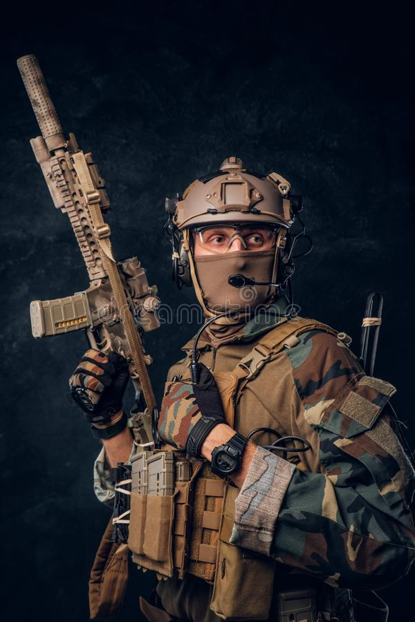 Elite unit, special forces soldier in camouflage uniform posing with assault rifle. Private security service contractor in camouflage uniform posing with stock image