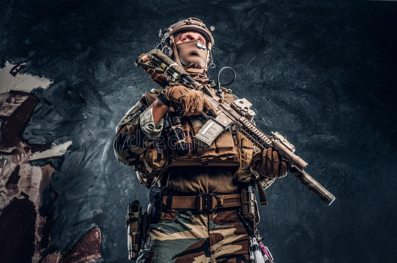Elite unit, special forces soldier in camouflage uniform posing with assault rifle. royalty free stock images