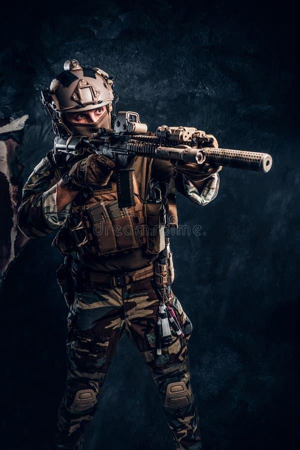 Eliteeenheid, speciale krachtenmilitair in camouflage eenvormige holding een aanvalsgeweer met een lasergezicht en doelstellingen royalty-vrije stock fotografie