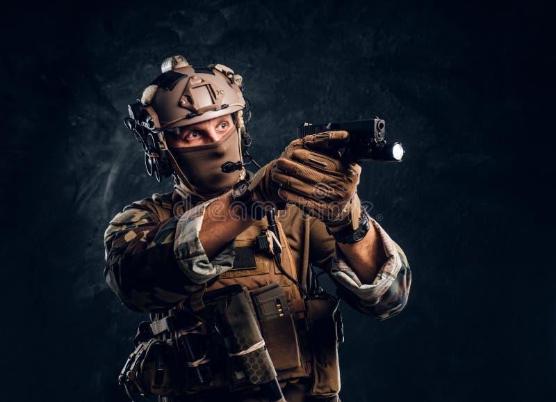 Elitenheten, specialf?rband tj?na som soldat i kamouflagelikformign som rymmer ett vapen med en ficklampa och laims p? m?let royaltyfri bild
