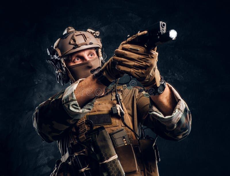 Elitenheten, specialf?rband tj?na som soldat i kamouflagelikformign som rymmer ett vapen med en ficklampa och laims p? m?let royaltyfri foto