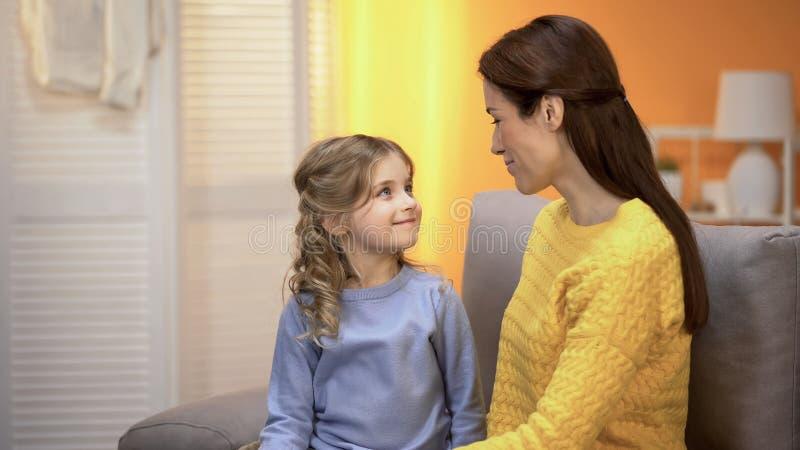 Elkaar bekijken en meisje en moeder die, speciale verbinding glimlachen stock foto