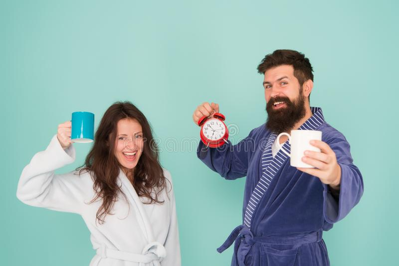 Elke ochtend begint met koffie Paar in badjassen met mokken De man met baard en de slaperige vrouw genieten ochtend van koffie of royalty-vrije stock foto's