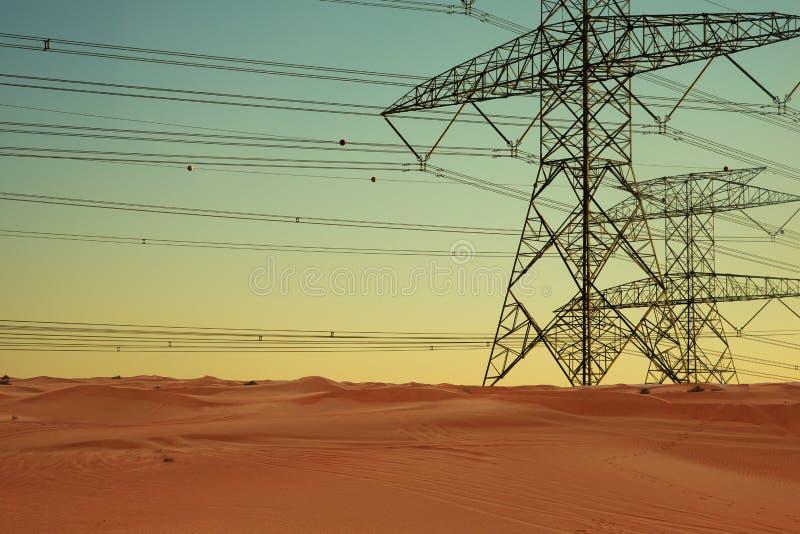 Elkraftlinjer och elektricitetsöverföringspyloner i öken på solnedgången royaltyfri bild