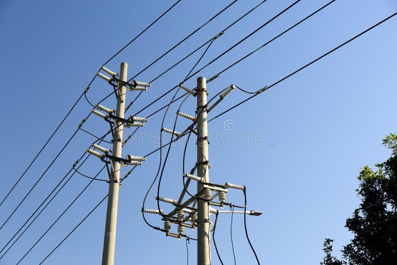Elkraftpol med linjer för elektricitetsmaktöverföring arkivbilder