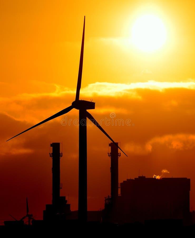Elkraftstation och vindturbin på soluppgång fotografering för bildbyråer