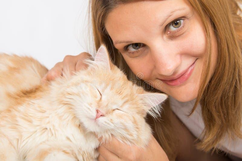 Ella acaricia su gato nacional foto de archivo