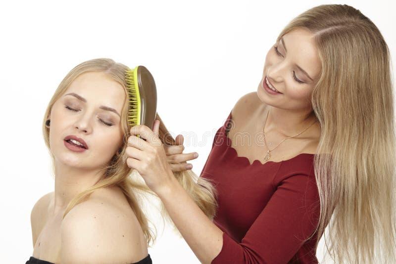 Ella cepilla a su novia el pelo fotografía de archivo