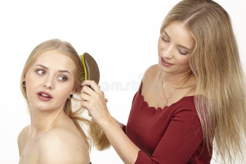 Ella cepilla a su novia el pelo fotos de archivo