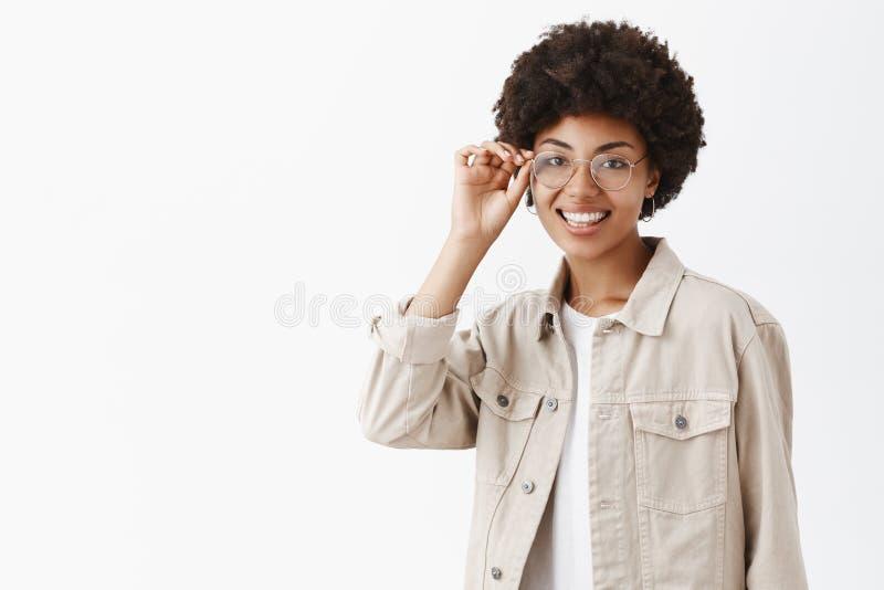 Ella conoce todo sobre estilo y la moda Estudio tirado de afroamericano feliz y femenino apuesto con afro foto de archivo libre de regalías