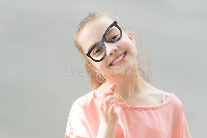 Ella está irradiando felicidad Pequeña muchacha sonriente con mirada divertida a través de los vidrios del apoyo Peque?o ni?o fel foto de archivo libre de regalías