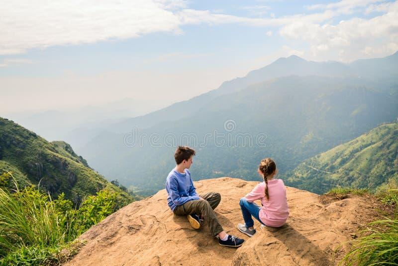 Ella gap views. Kids enjoying breathtaking views over mountains and tea plantations from Little Adams peak in Ella Sri Lanka royalty free stock photography