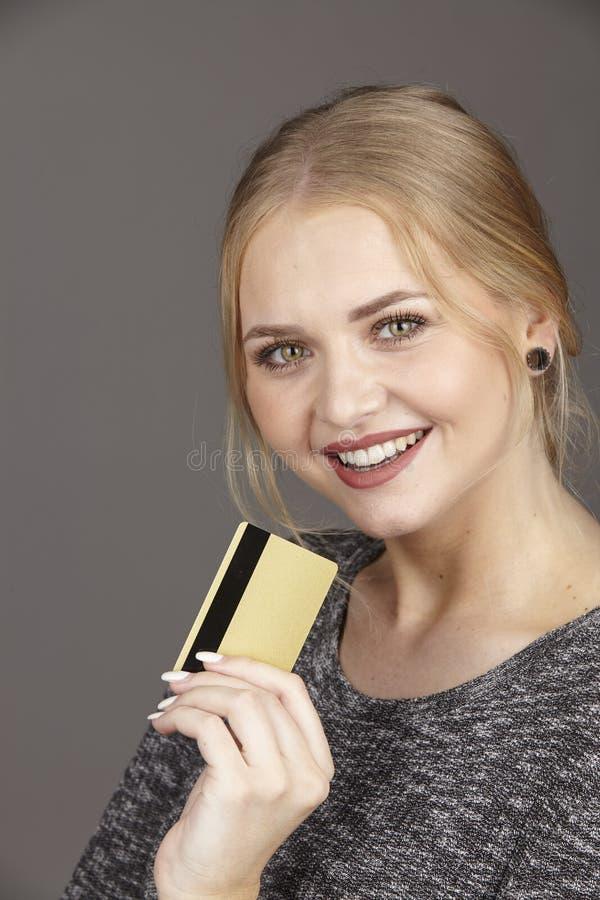 Ella gasta mucho dinero por la tarjeta de crédito de oro imagen de archivo