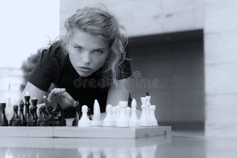 Ella golpea los pedazos de ajedrez del tablero fotos de archivo