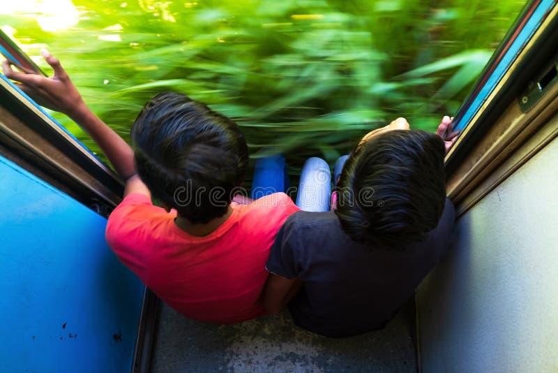 Ella Sri Lanka 17 April 2018: Två tonår som rider på drevet för 2 grupp och utanför ser fotografering för bildbyråer