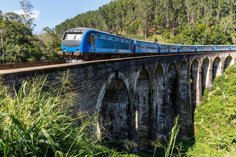 Train on railway road and various trees with green foliage in Asia. ELLA, SRI LANKA - JAN 17, 2017: train on railway road and various trees with green foliage in stock photography