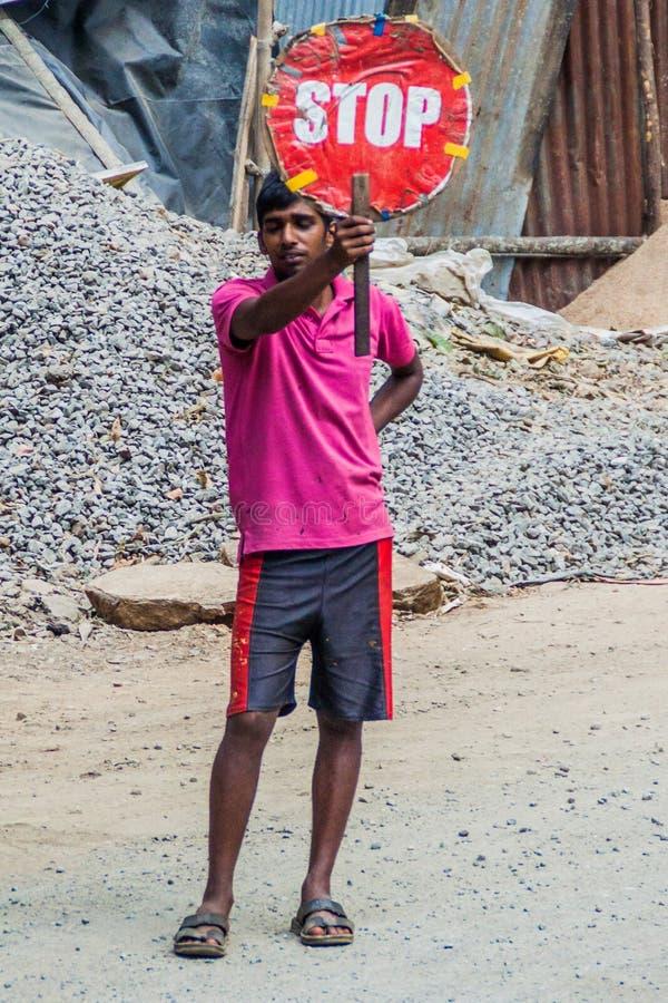 ELLA, SRI LANKA - JULY 14, 2016: Local worker holding a stop sign near Ella villag royalty free stock photography