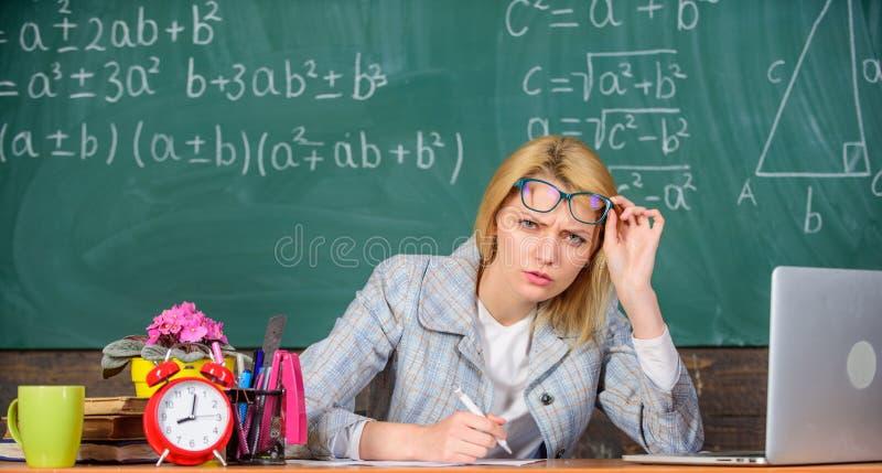 Ella tiene dudas en su informe o conocimiento La mujer del profesor sienta el fondo de la pizarra de la sala de clase de la tabla fotos de archivo libres de regalías