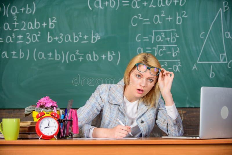 Ella tiene dudas en su informe o conocimiento Profesor que mira a escondidas sospechoso de las lentes La mujer del profesor sient imagen de archivo