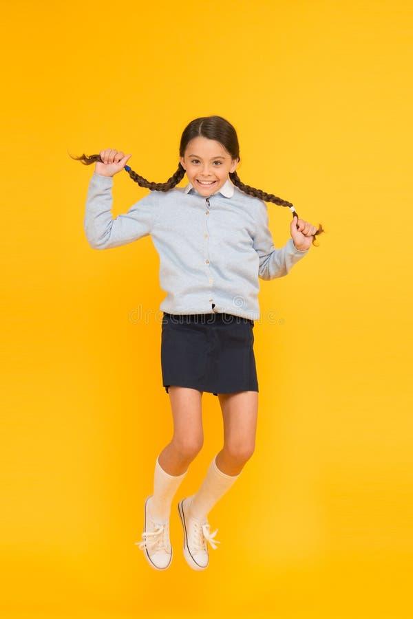 Elle est hyper Enfant énergique heureux sautant sur le fond jaune Petite fille avec long sentiment de tresses de cheveux énergiqu image libre de droits