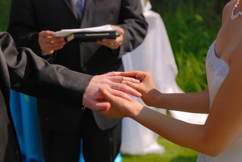 Elle met la boucle de mariage sur lui photos libres de droits