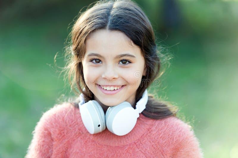 Elle ressemble à un mélomane Petite fille adorable extérieure Peu écouteurs de port d'enfant de fille L'enfant heureux apprécient image stock