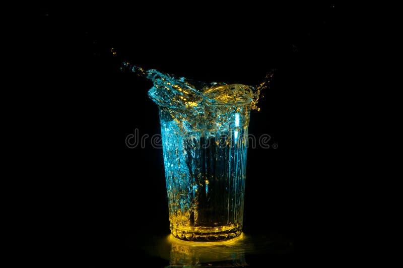 Ellipse de l'eau éclaboussant hors d'un verre strié sous les lumières jaunes et bleues d'isolement sur un fond noir photo stock