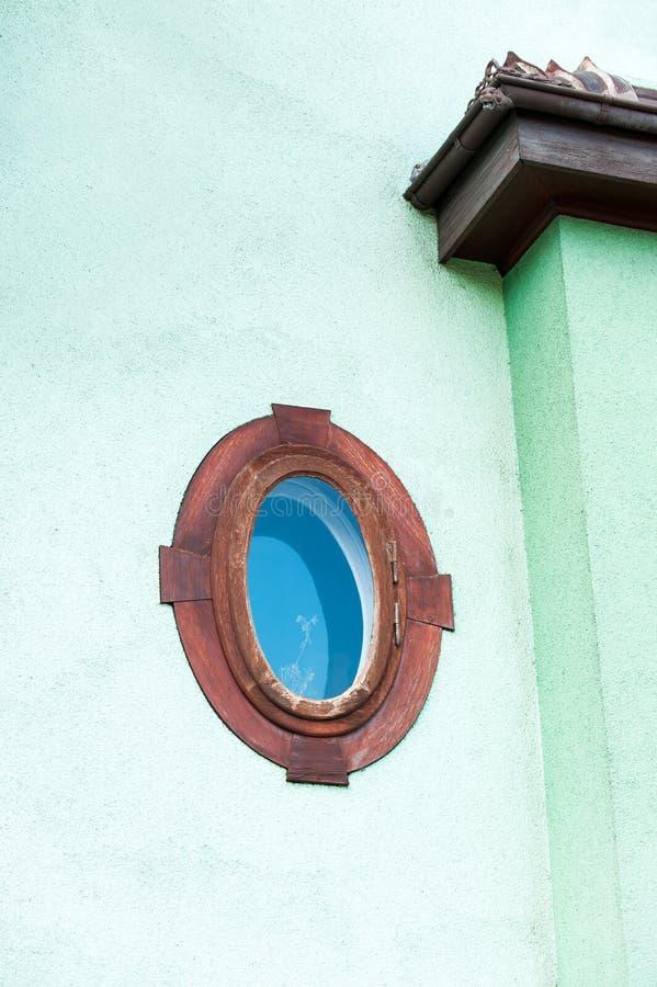 Ellipse formte Fenster im roten Holzrahmen auf mehrfarbigem Grün lizenzfreie stockbilder