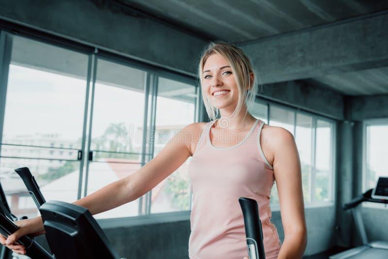 Elliptische de traineroefening van de vrouwentraining in geschiktheidsgymnastiek , Portret van vrij aantrekkelijke Kaukasische vr stock afbeeldingen