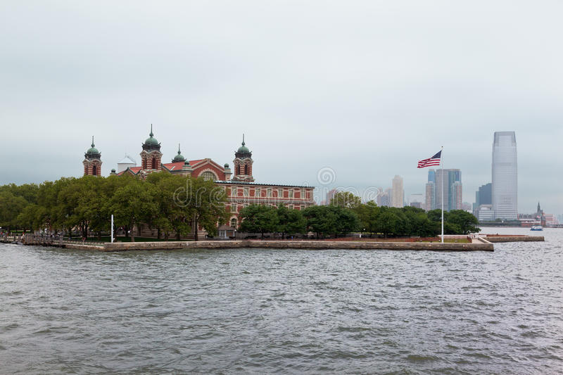Ellis Island New York City. Ellis Island building with its four green copper towers an american flag and the modern glass tower buildings of New Jersey in the royalty free stock images