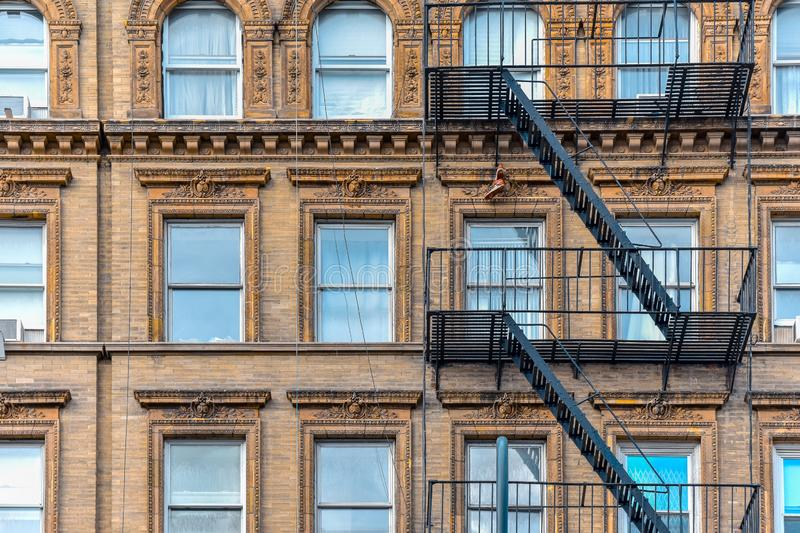 Ellow brick facade, and pair of boots hanging of the fire stairs. Chelsea, NYC. Yellow brick facade, and pair of boots hanging of the fire stairs. Chelsea, NYC royalty free stock photo